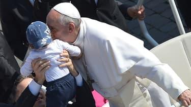 Le pape François embrasse un enfant place Saint-Pierre au Vatican le 8 mai 2013.