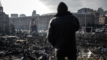 Des Ukrainiens se réunissent sur la place de l'Indépendance qui porte encore les traces des combats de la veille.