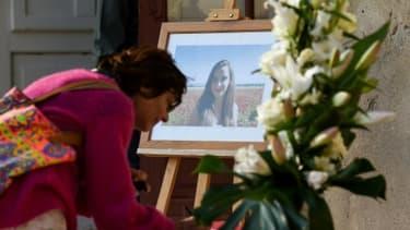 Une femme écrit un message de condoléance à côté du portait de Mauranne, à Eguilles, le 2 octobre 2017