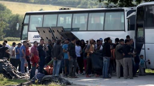 Des migrants montent à bord d'un bus le 23 mars 2016 à Idomeni
