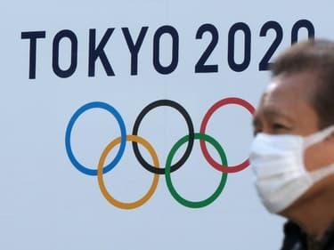 Un homme portant un masque passe devant le logo des Jeux olympiques de Tokyo le 4 février 2021