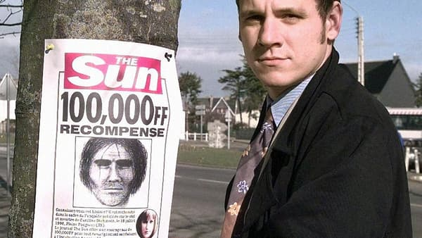 Un journaliste britannique pose à côté d'un avis de recherche du suspect dans l'affaire Dickinson.
