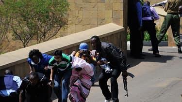 Des policiers évacuent des clients du centre commercial, samedi après-midi, à Nairobi.