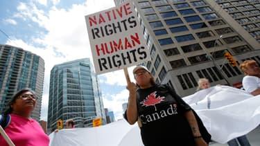 """Une femme tient une pancarte """"Droits des Amérindiens = Droits humains"""" lors d'une manifestation à Toronto, le 24 juin 2010."""