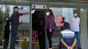 Un agent de sécurité prend la température d'une femme avant qu'elle entre dans un centre commercial, le 8 juin 2020 à Siliguri, en Inde