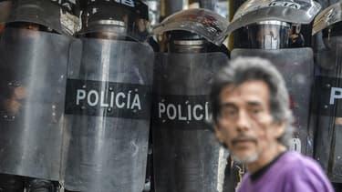 Un manifestant devant des policiers lors d'un rassemblement contre le président Nicolas Maduro, le 20 mai 2017 au Venezuela.