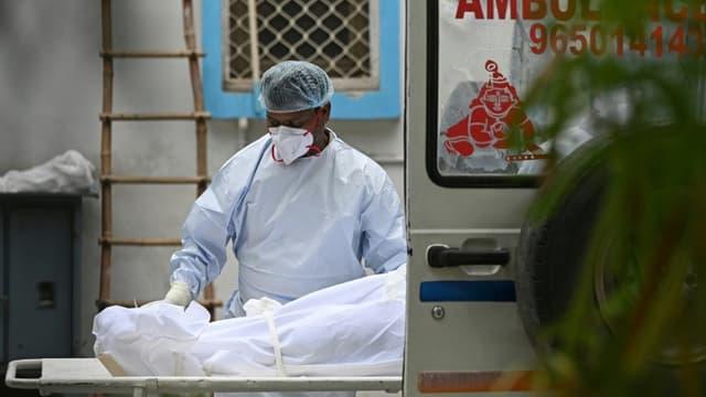 Le corps d'une personne décédée du Covid-19 est chargé dans une ambulance pour le transporter à la morgue, le 18 mai 2021 à New Delhi, en Inde