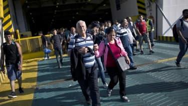 Des migrants débarquent au port du Pirée, le 29 août 2015, en Grèce