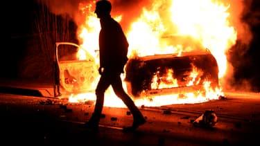 Un manifestant passe devant une voiture brûlée à Ferguson, dans la nuit de lundi à mardi.