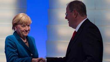 Angela Merkel serre la main à son rival Peer Steinbrück après sa victoire. Les deux partis, CDU et SPD, sont d'accord pour gouverner ensemble.