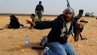 Rebelles tentant de s'abriter du pilonnage par les forces fidèles à Mouammar Kadhafi près de Ras Lanouf, vendredi. Les combats de vendredi semblent confirmer la partition de la Libye entre l'Ouest du pays, autour de la capitale, Tripoli, sous le contrôle
