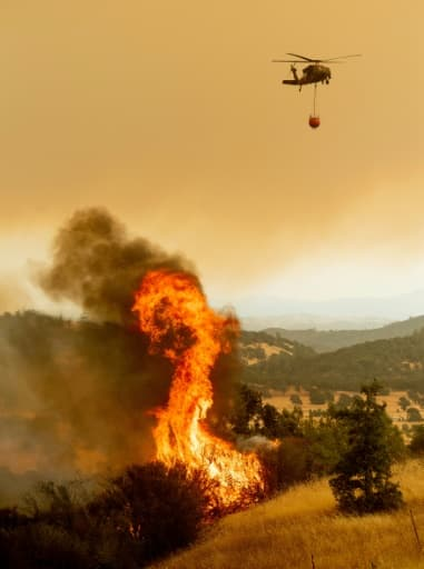 Un hélicoptère se prépare à arroser d'eau l'incendie Ranch Fire, partie du Mendocino Complex, qui enflamme la route de High Valley, près de Clearlake Oaks, en Californie.