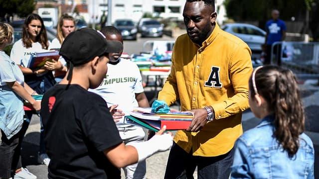 Le rappeur Mac Tyer distribuant des fournitures scolaires à des enfants d'Aubervilliers en Seine-Saint-Denis.