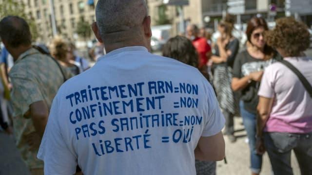 Un opposant au  pass sanitaire et à la vaccination manifeste avec d'autres soignants devant l'hôpital de la Timone à Marseille, le 5 août 2021