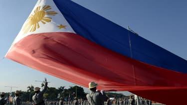 Les gardes d'honneur philippins hissent un drapeau géant pendant le 119e anniversaire de la mort du héros national José Rizal au parc Luneta, à Manille le 30 décembre 2015.