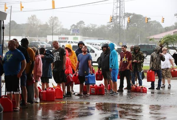 Des habitants de Caroline du Nord font la queue pour acheter de l'essence à une station endommagée, le 15 septembre 2018 à Wilmington.