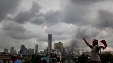 Manifestants antigouvernementaux près d'une barricade en flammes à Bangkok, dimanche. Le Premier ministre thaïlandais, Abhisit Vejjajiva, a déclaré que son gouvernement étudiait la possibilité de décréter un couvre-feu dans la capitale après trois jours d