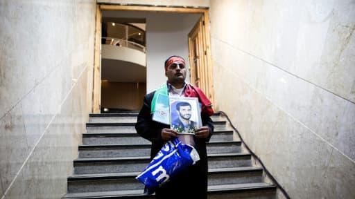Rassoul Allahyari pose avec le portrait du Président sortant Mahmoud Ahmadinejad, alors qu'il dépose sa candidature à la prochaine élection présidententielle au ministère de l'Intérieur, le 7 mai 2013.