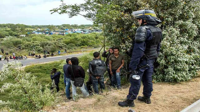 Un CRS se tenant devant un groupe de migrants (illustration)
