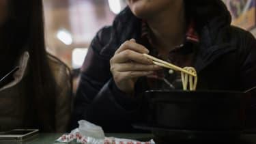 Une femme mange des nouilles dans un restaurant de Pékin (Chine) le 19 novembre 2014.