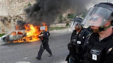 Véhicule en flamme près de la Vieille ville de Jérusalem, mercredi. Des policiers israéliens ont pénétré mercredi dans le complexe de la mosquée al Aksa, dans la Ville Sainte, pour disperser des Palestiniens qui lançaient des pierres en direction du mur d