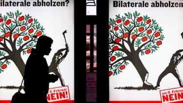 """Une personne passe devant une affiche contre """"l'immigration de masse"""", à Zurich."""