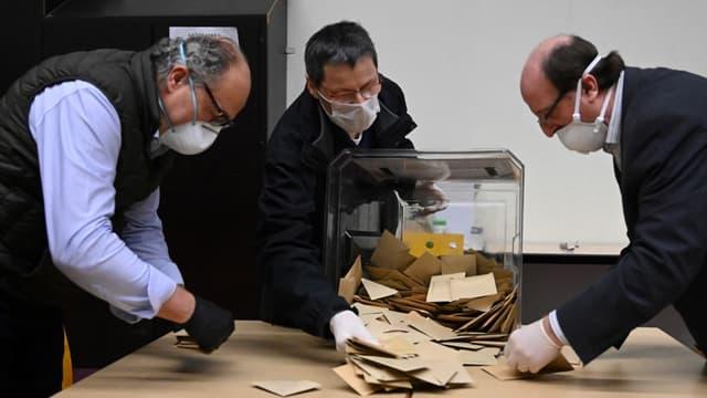 Des assesseurs portant des masques lors du dépouillement du premier tour des élections municipales, le 15 mars 2020