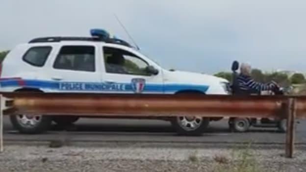 Des policiers municipaux escortent un individu en fauteuil roulant en le poussant, le 30 août 2015, à Leucate.