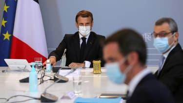 Le président Emmanuel Macron lors d'un conseil de défense avec le ministre de la Santé Olivier Véran (2è d) et le secrétaire général de l'Elysée Alexis Kohler (d), à l'Elysée, le 12 novembre 2020