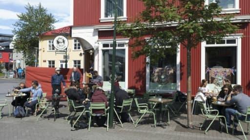 Des touristes assis à la terrasse d'un café à Reykjavik le 1er juillet 2016