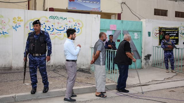 Des Irakiens attendent devant un bureau de vote, le 12 mai 2018, à Bagdad.