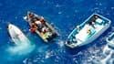 Des membres de l'ONG Greenpeace (à gauche) secourent un de leurs collègues dont le bateau a chaviré. Les écologistes tentaient de s'opposer à des pêcheurs (à droite) capturant des thons rouges en mer Méditerranée. /Photo prise le 4 juin 2010/REUTERS/Paul