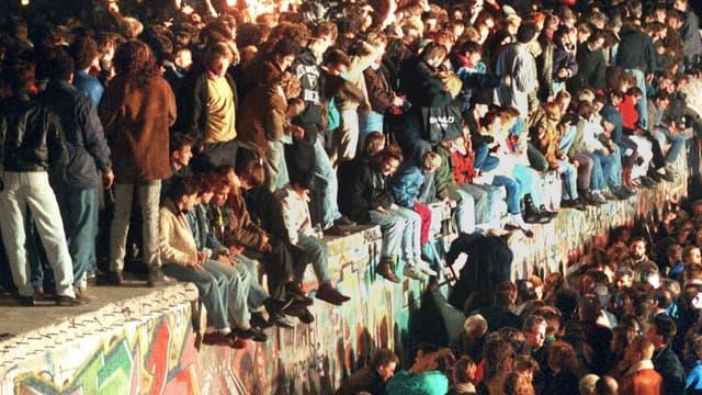 Des Allemands assis sur le Mur de Berlin, le 11 novembre 1989.