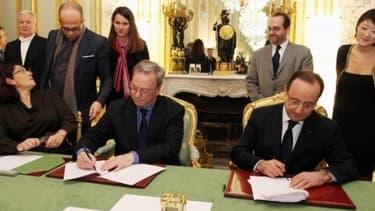 François Hollande signant un accord sur la presse avec Eric Schmidt (Google) il y a un an.