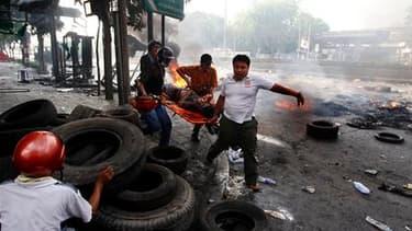 Evacuation d'un homme touché par une balle samedi à Bangkok. Selon le centre médical public Erawan, le bilan des affrontements qui opposent depuis deux jours l'armée thaïlandaise à des manifestants hostiles au gouvernement s'élève désormais à 22 morts. /P