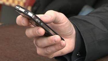 Un homme utilise son téléphone mobile.