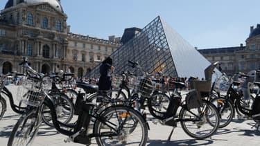 Des vélos électriques devant la pyramide du Louvre.