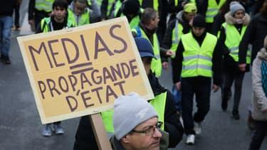 """Un manifestant tient une pancarte """"Médias = propagande d'Etat"""" le 12 janvier 2019 à Paris."""