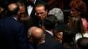 Silvio Berlusconi discutant avec des débutés lors des débats sur le plan d'austérité. Après les sénateurs la veille, les députés italiens ont adopté à leur tour, vendredi, le plan d'austérité présenté par le gouvernement, qui prévoit 48 milliards d'euros
