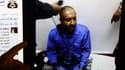 Un homme montre la page Facebook de la brigade révolutionnaire de Tripoli, montrant Saadi Kadhafi en train d'être rasé.