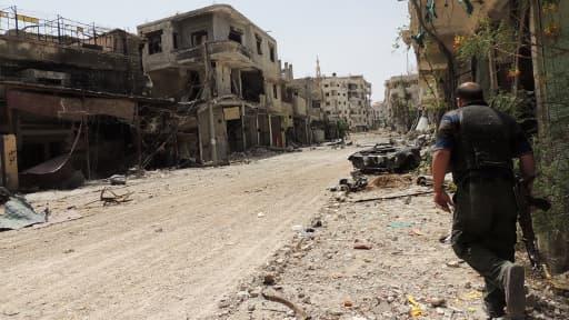 Un rebelle marchant dans les ruines de banlieue de Damas, le 25 mai 2013.