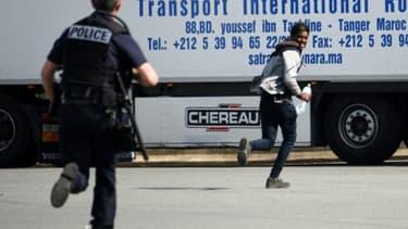 Un policier poursuit un jeune homme suspecté d'être un migrant, dans les environs de Calais le 5 juillet 2017