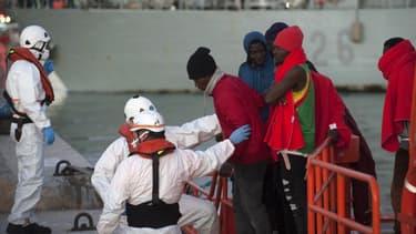 Des migrants descendent d'un bateau des garde-côtes dans le port de Malaga en Espagne, le 7 décembre 2017.