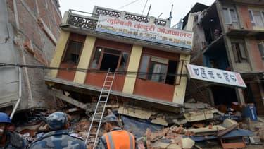 Des secours regardent un immeuble sérieusement endommagé par le séisme, le 26 avril, à Katmandou, au Népal.