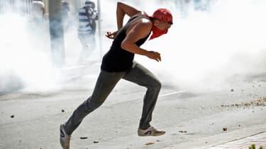 Un manifestant brésilien, jeudi, tente d'échapper aux gaz lacrymogènes des policiers.