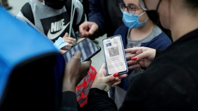 Un salarié de la SNCF contrôle le pass sanitaire d'un passager sur son téléphone portable à la gare de Lyon à Paris, le 9 août 2021