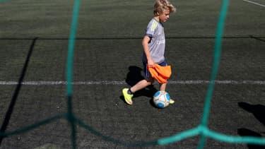 Un enfant joue au football sur du gazon artificiel en Croatie en avril 2016