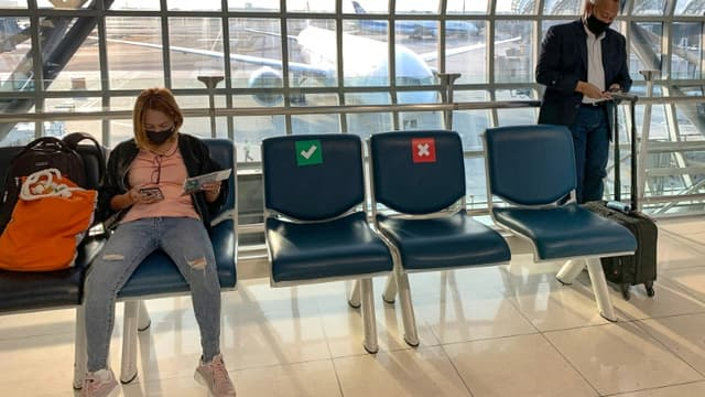 Des sièges marqués d'une croix rouge pour respecter la distanciation physique entre les passagers dans une salle d'embarquement à l'aéroport de Bangkok, le 31 mars 2021 en Thailande