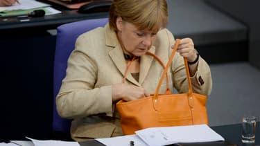 Angela Merkel avec un modèle orangé du sac Le Foulonné de Longchamp.