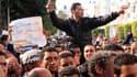 Un homme, à Tunis, avec un sèche-cheveu en référence à l'ex-première dame de Tunisie Leïla Trabilsi lors d'une manifestation appelant à former un gouvernement sans membres ayant officié sous le régime de Zine Ben Ali. La télévision locale a en outre annon